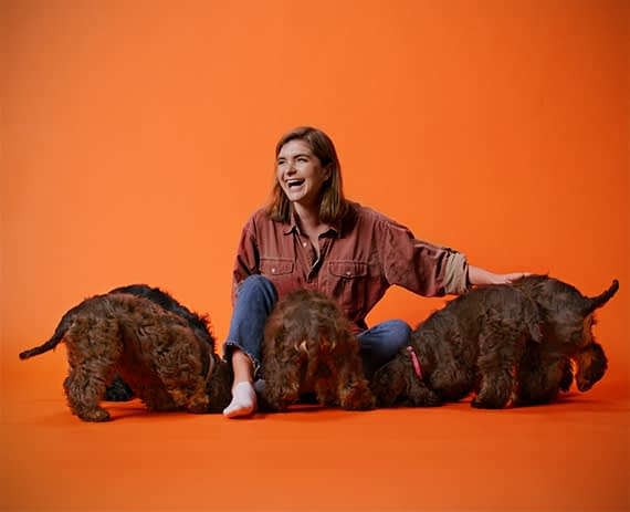 Fanny schoug laughing and playing with three brown american cocker spaniel dogs